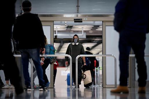 Imagen de un pasajero en a la terminal de llegadas de un aeropuerto.