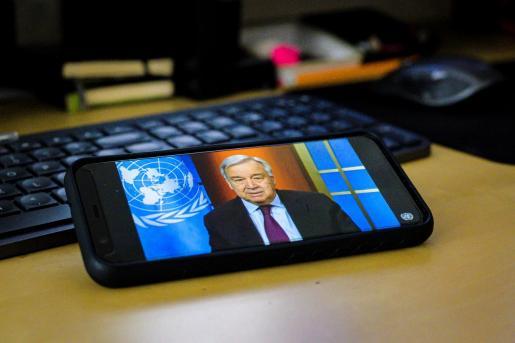Fotografía cedida por la ONU donde aparece un teléfono móvil con la imagen de su secretario general, António Guterres, mientras habla este jueves mediante una conferencia de prensa virtual.