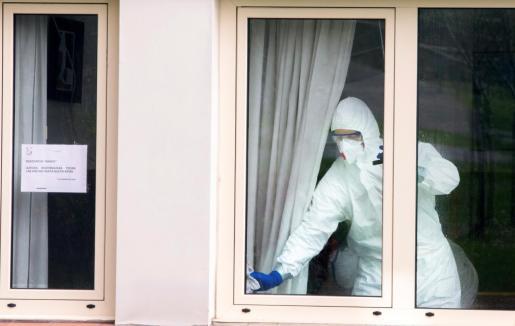 Un operario limpia una habitación de una residencia.