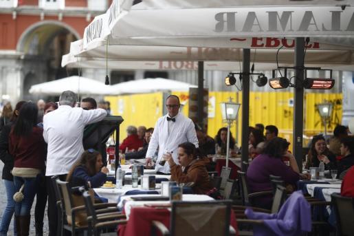 Imagen de camareros trabajando en una terraza de la Plaza Mayor.