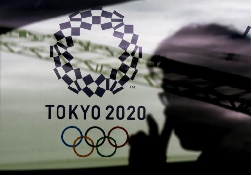 Un conductos observa el logotipo de los Juegos Olímpicos de Tokio.