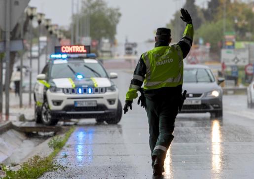 Un agente de la Guardia Civil de Tráfico de la Comandancia de Sevilla da el alto a un conductor durante un control.