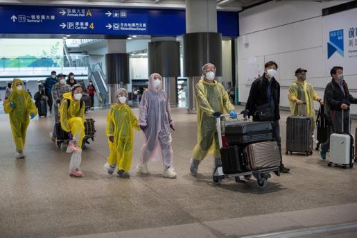 Una familia se protege a su llegada al aeropuerto de Hong Kong.
