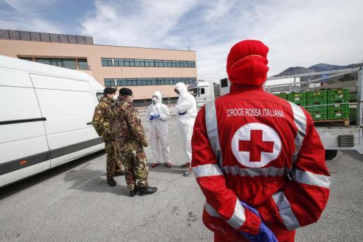 Un miembro de la Cruz Roja junto a militares y personal sanitario.