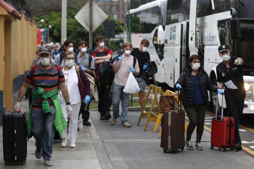 Ciudadanos españoles esperando los autobuses que los llevarán al aeropuerto a tomar un avión de repatriación de Iberia este miércoles, en Lima.