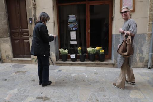 Dos vecinas de la zona se acercaron a la tienda para recoger las flores depositadas en la puerta. En un cartel se podía leer «Llévame» y se pedía que cada ciudadano se llevara un único ramo.