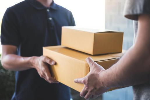 Un mensajero hace entrega de un paquete a un cliente.