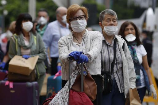 Ciudadanos españoles esperan en Perú los autobuses que los llevarán al aeropuerto a tomar un avión de repatriación.