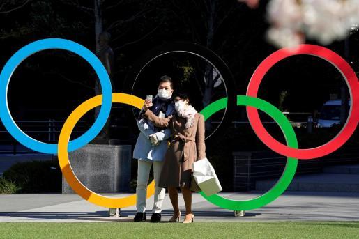 Una pareja con máscaras protectoras se toma selfies de un monumento de los Anillos Olímpicos frente a la sede del Comité Olímpico de Japón en Tokio, Japón.