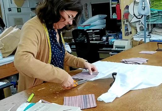 Una empleada corta la tela en Teixits Vicenç.