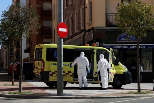 Dos trabajadores sanitarios con trajes protectores salen de una ambulancia en Salamanca.