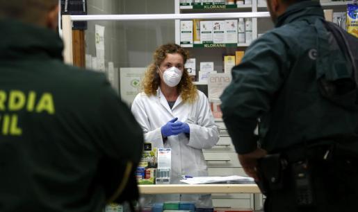 Dos guardias civiles, en una farmacia de Pollença.