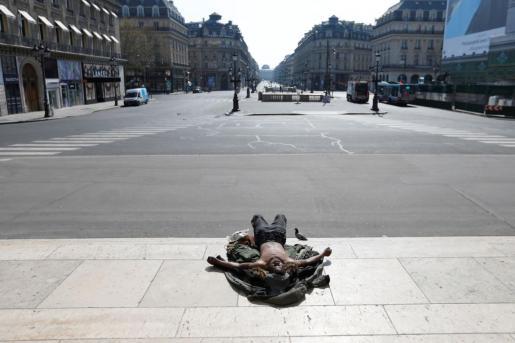 Un sin techo tumbado en la acera de la Plaza de la Ópera con las calles vacías de fondo.