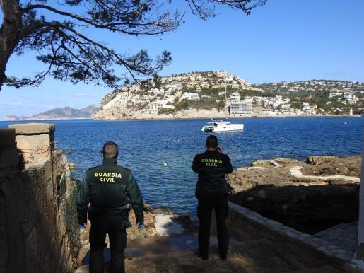 Dos agentes de la Guardia Civil observan el catamarán en Cala Egos.