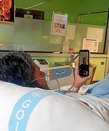 Un paciente, habla por el móvil con un familar desde su cama en Son Llàtzer.