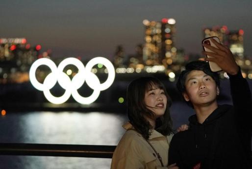 Una pareja se fotograía junto a los aros olímpicos instalados en la bahía de Tokio.