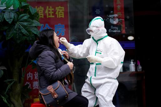 Un sanitario, realizando un test a una ciudadana china.