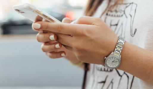 Una adolescente observa su teléfono móvil.