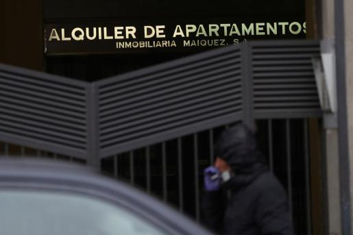 Un hombre pasa ante unos apartamentos de alquiler.
