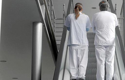Dos sanitarios charlan mientras suben las escaleras mecánicas de su hospital.