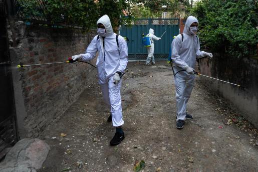 Dos personas realizando tareas de desinfección.
