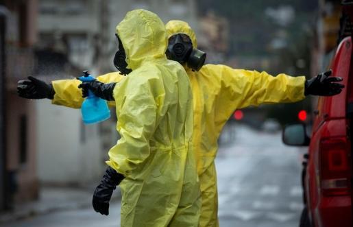 Miembros de la Unidad Militar de Emergencia (UME) se desinfectan tras trabajan en el desinfectado una residencia geriátrica de Palleja (Barcelona).