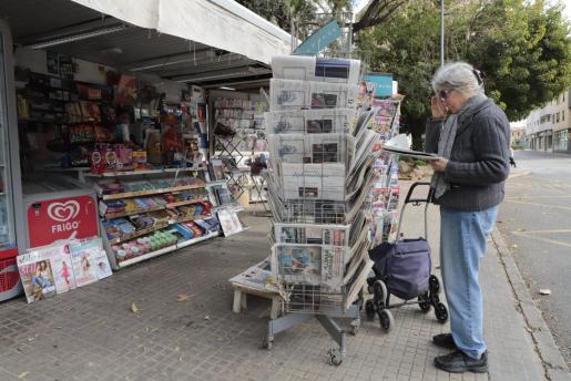 Una mujer, frente a uno de los pocos quioscos de prensa que hay abiertos en Palma.