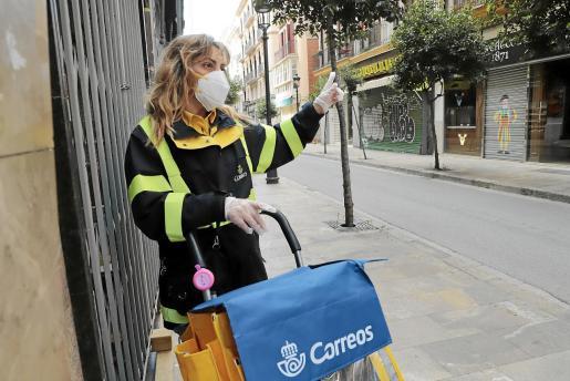 Carmen, con su bolsa, repartiendo cartas por la calle Colom de Palma.