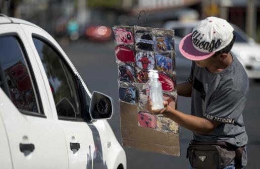 """ACOMPAÑA CRÓNICA: CORONAVIRUS NICARAGUA - AME113. MANAGUA (NICARAGUA), 03/04/2020.- Un joven vende mascarillas de tela y gel antibacterial como medida de prevención contra la propagación del coronavirus este viernes, en Managua (Nicaragua). La solidaridad ha aflorado en calles y mercados de Nicaragua en medio de la crisis causada por la COVID-19. Jabones, mascarillas, alcohol en gel, y hasta viajes en autobús gratuitos, son ofrecidos por algunos ciudadanos para prevenir o mitigar el impacto de la pandemia. """"Su vida interesa, tome jabón si lo necesita"""", """"Mascarillas gratis, tomá 1, recordá que todos necesitamos"""", se lee en hojas de papel pegadas en las paredes exteriores de algunos establecimientos comerciales o ventas de verduras, para el provecho de los visitantes. EFE/ Jorge Torres Solidaridad aflora en calles y mercados de Nicaragua ante la COVID-19"""