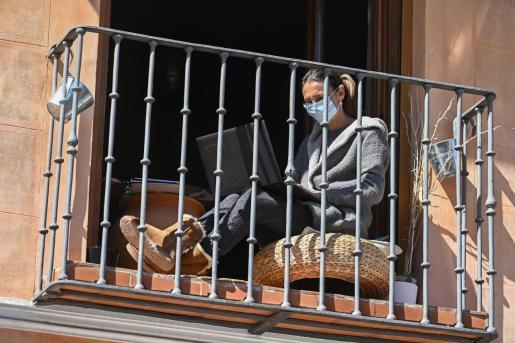 Una mujer en el balcón de su vivienda en Alcalá de Henares, durante el estado de alarma por la epidemia del coronavirus.