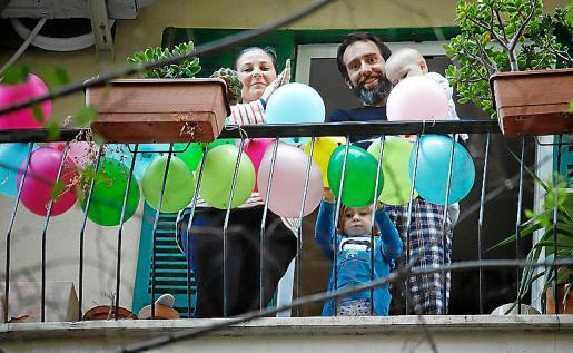 Una familia aplaude desde el balcón de su casa a las ocho de la tarde.