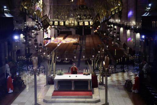 El obispo de Mallorca, de espaldas, y la Catedrla de Mallorca vacía, sin fieles.