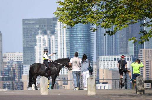 Una agente de la policía montada advierte a unos ciudadanos en Greenwich Park de Londres.