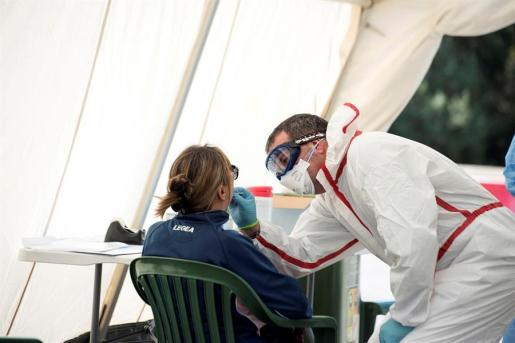 Un sanitario realizada un prueba de extracción a una paciente para la detección del coronavirus.
