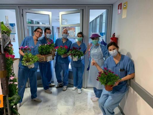 Varios profesionales sanitarios de Son Espases muestra las flores que recibieron como regalo.
