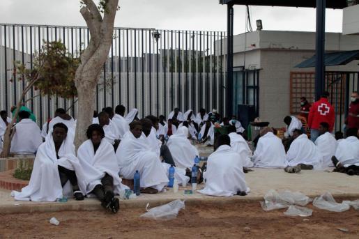 Unos cincuenta inmigrantes descansan tras conseguir saltar la valla, que separa la ciudad autónoma de Melilla de Marruecos, este lunes.