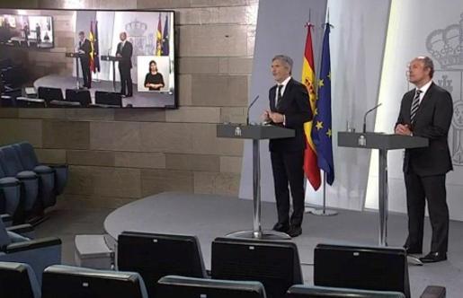 Captura de la señal institucional de Moncloa del ministro de Justicia, Juan Carlos Campo (d) y el titular de Interior, Fernando Grande-Marlaska, durante la rueda de prensa.