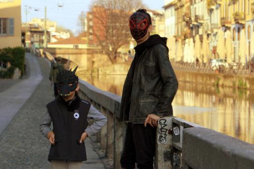 Una padre junto a su hijo con máscaras en Milán.