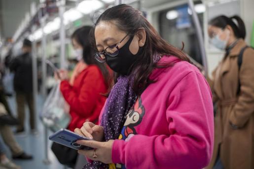 Una ciudadana china viaja en el metro protegida con su mascarilla.