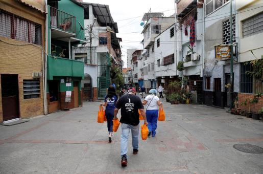 Trabajadores de Chacao caminan con bolsas de comida para los ancianos durante la cuarentena en Venezuela.