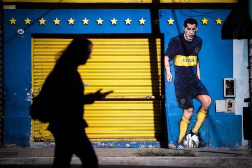 Silueta de una mujer que camina frente a una pintada de Juan Román Riquelme, en el barrio de la Boca.