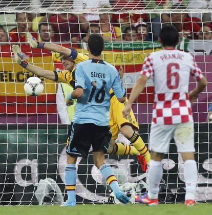 El portero de España Iker Casillas (i, detrás) despeja el balón en presencia de su compañero Sergio Busquets y del centrocampista de Croacia Danijel Pranjic.