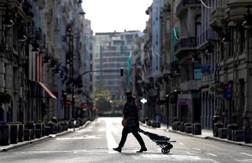 Una señora con mascarilla y carro de la compra en una calle desierta.