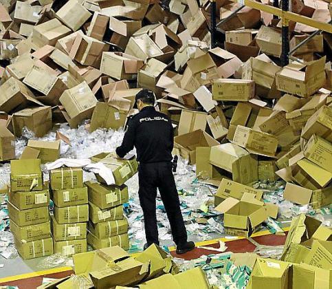 Un policía participa en la redada de material sanitario realizado en el interior de una nave del polígono del Tambre en Santiago de Compostela.