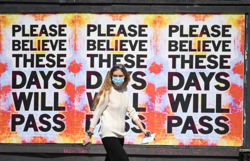 London (United Kingdom), 09/04/2020.- A woman wearing a protective face mask passes an artwork attributed to Mark Tichner and displayed on billboards in east London, Britain, 09 April 2020. Countries around the world are taking increased measures to stem the widespread of the SARS-CoV-2 coronavirus which causes the Covid-19 disease. (Reino Unido, Londres) EFE/EPA/NEIL HALL Coronavirus in Britain