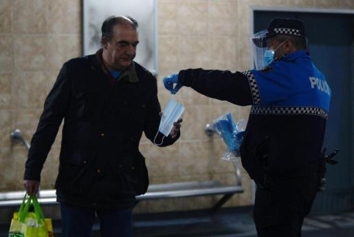 Un hombre coge una mascarilla de manos de un policía municipal, momentos antes de subirse al autobús, camino de su puesto de trabajo este lunes en la ciudad de Valladolid.