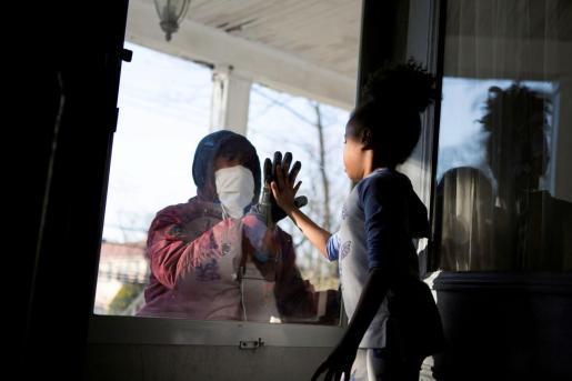 Hashim, un trabajador esencial en la industria de la salud, saluda a su hija a través de la puerta cerrada mientras mantiene la distancia social de su familia.
