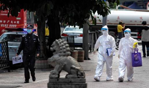Dos ciudadanos, totalmente cubiertos, caminan por una calle de Wuhan.