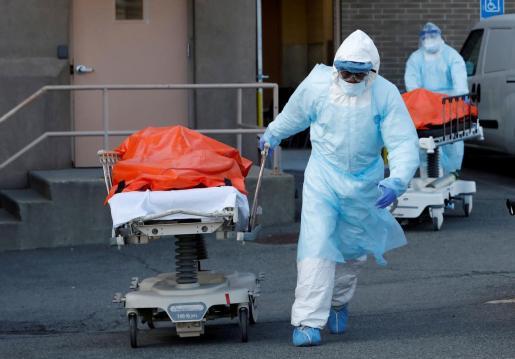 Personal médico trasladando a fallecidos por el virus.