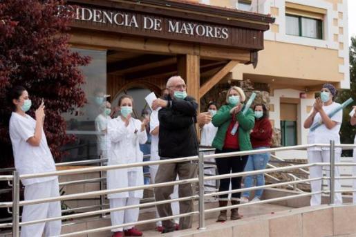 El personal sanitario despide a un enfermo que ha superado el coronavirus en una residencia de mayores.